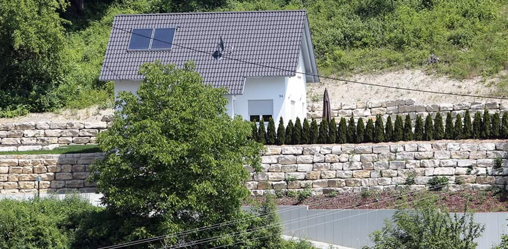 Hangsicherung mit Jura-Kalkstein und Betonstützwand.